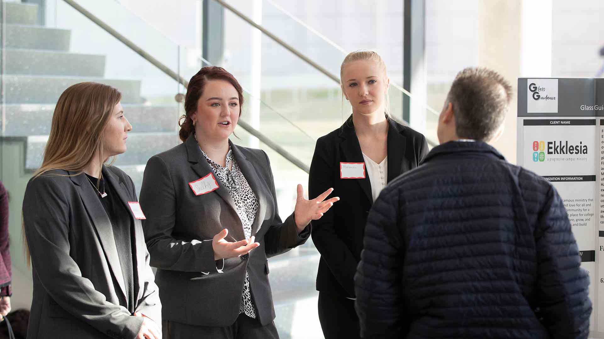 Management students presenting at symposium in Glass Hall atrium